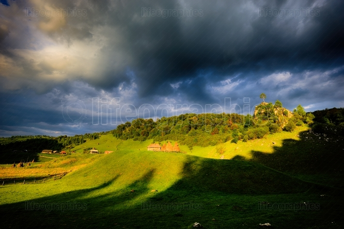 Rural landscape with house in summer sunrise light somewhere in transylvania romania. heavy storm aproaching