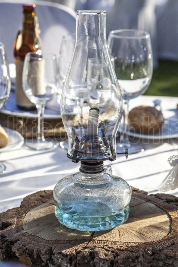 Rustic kerosene lamp over log cut as a wedding centerpiece table