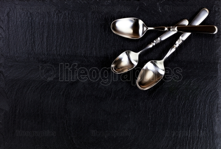 Rustic spoons on slate stone background