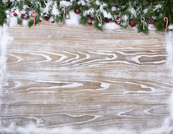 Rustic white wooden boards with snowy fir branches for Christmas