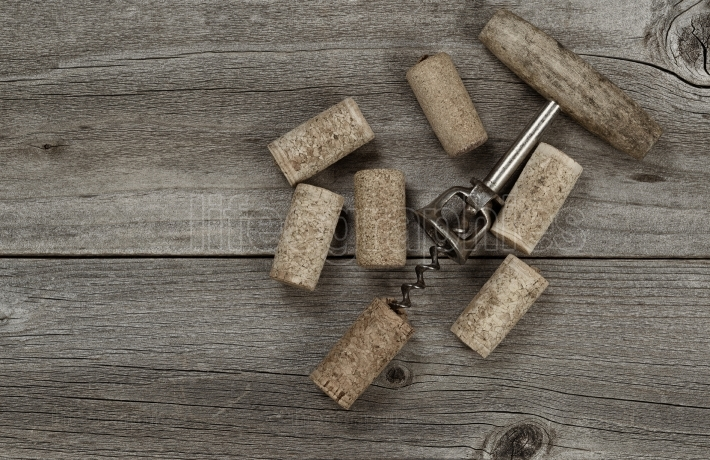 Rustic Wine Opener with used corks on aged wood