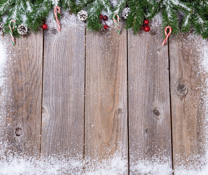 Rustic wooden boards with snow covered fir branches for Xmas con