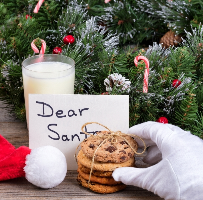Santa Claus hand reaching for a cookie with holiday decorations
