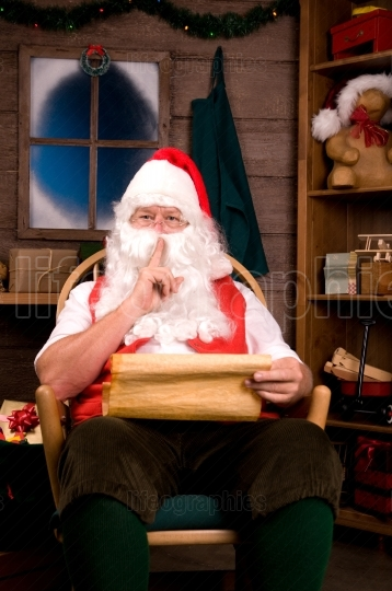 Santa Claus in Rocking Chair with Naughty List Going Shh