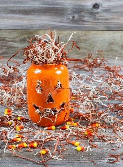 Scary large orange pumpkin ceramic jar on rustic wood