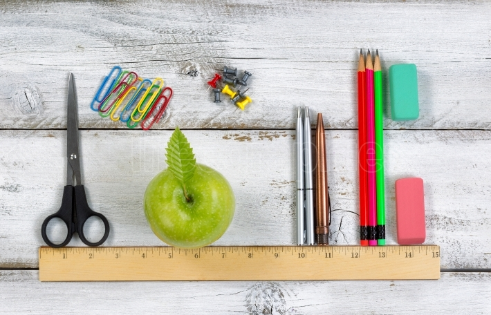 School supplies in line with ruler on white desktop
