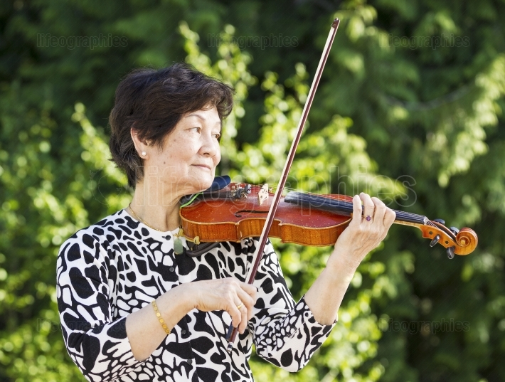 Senior Asian Woman Playing Violin outdoors