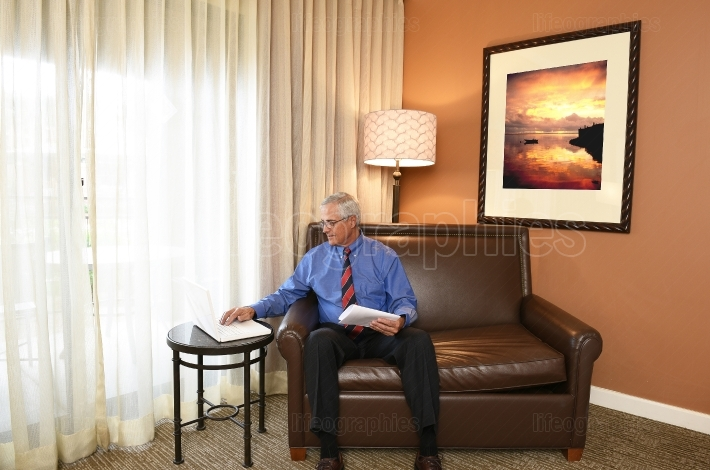 Senior Businessman at Work in Hotel Room