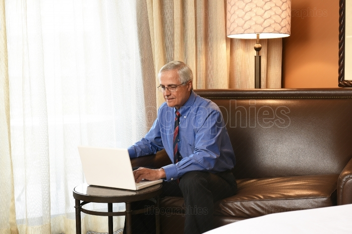Senior Businessman Working in Hotel Room