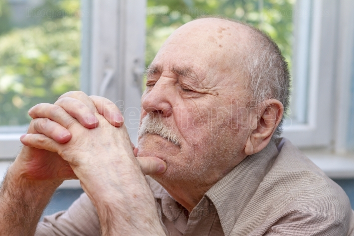 Senior man thinking and praying