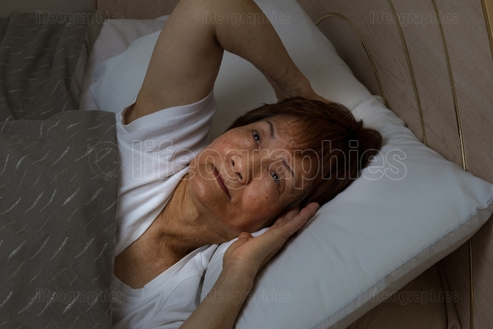 Senior woman cannot sleep at nighttime due to insomnia