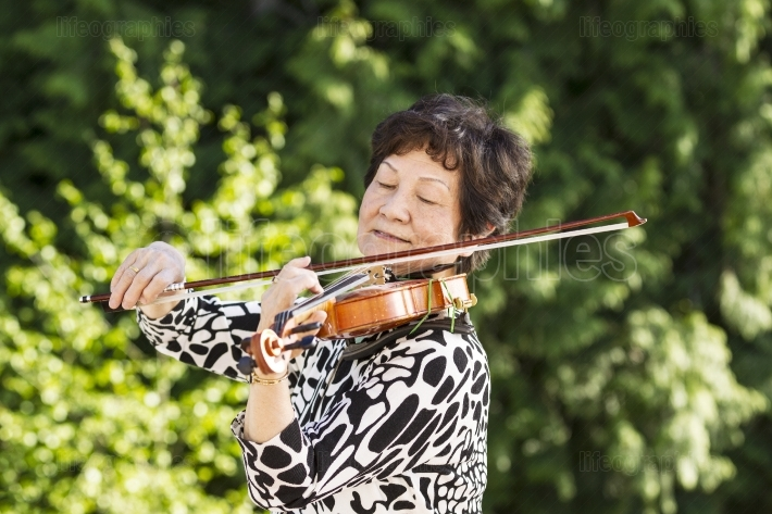 Senior woman concentrating while playing music outdoors