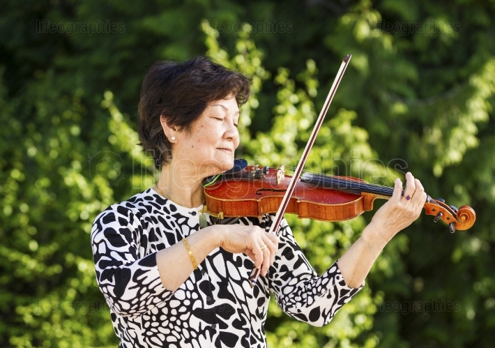 Senior woman focused with eyes closed while playing music outdoo