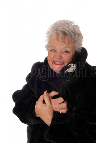 Senior woman having fun with her fur coat.