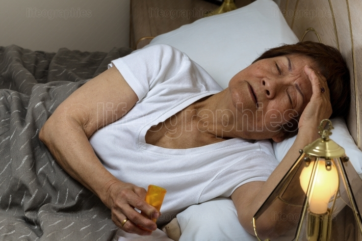 Senior woman preparing to take medicine at nighttime due to inso