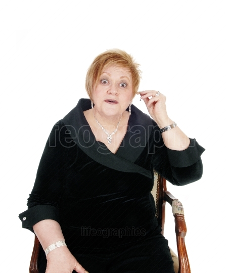 Senior woman putting hearing aid on.