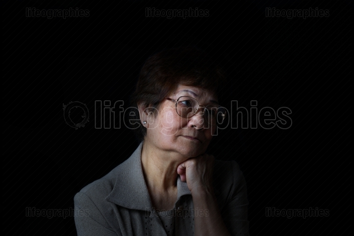 Senior woman resting head while looking depressed on black backg