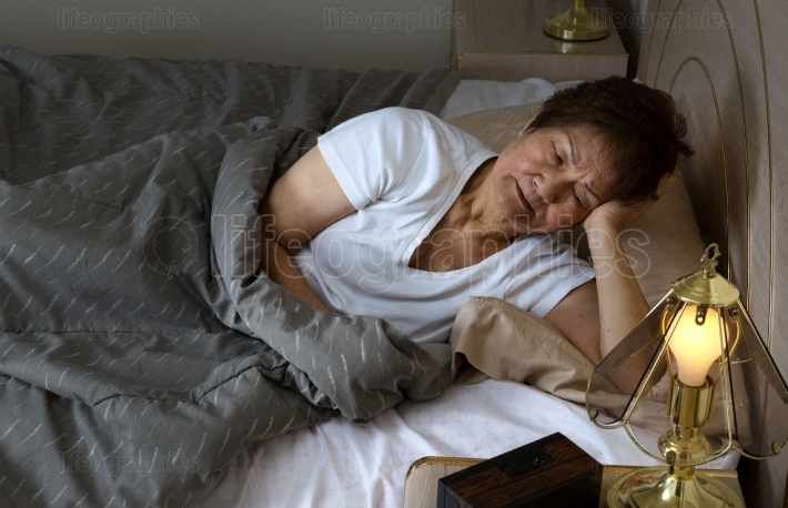 Senior woman restless at nighttime while trying to sleep