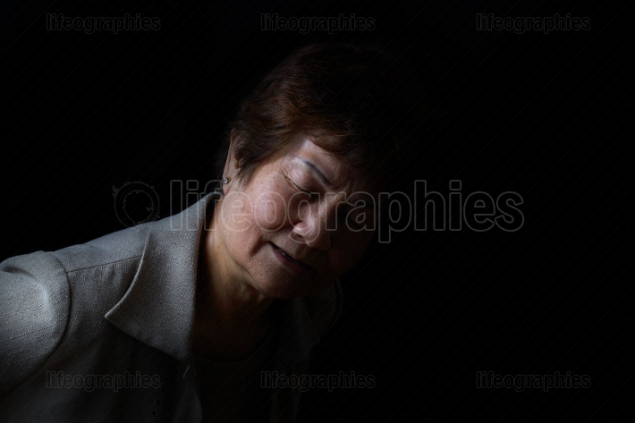 Senior woman showing back pain on black background