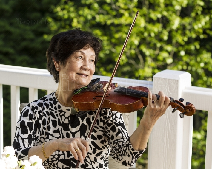 Senior woman sitting down while playing her violin outdoors