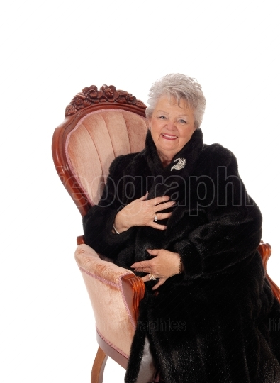 Senior woman sitting in armchair.