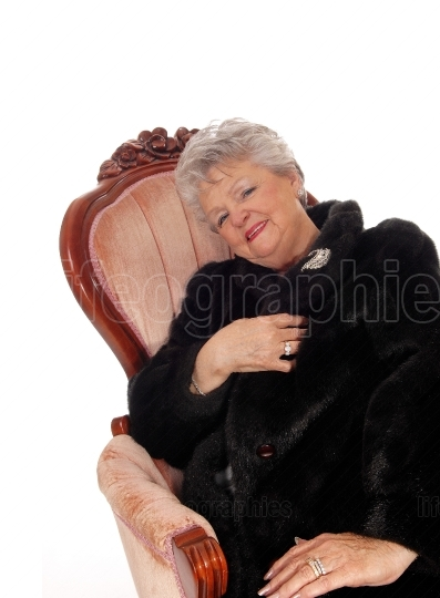 Senior woman sitting in pink armchair.