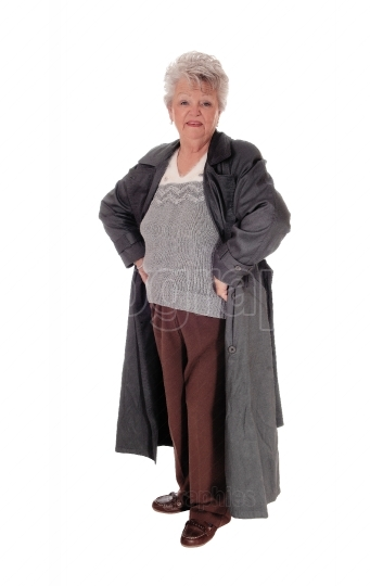 Senior woman standing in a coat.