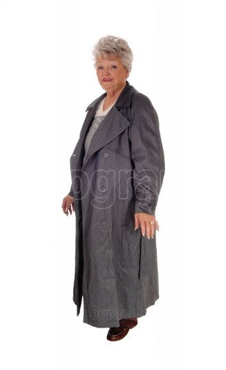 Senior woman standing in a long coat.