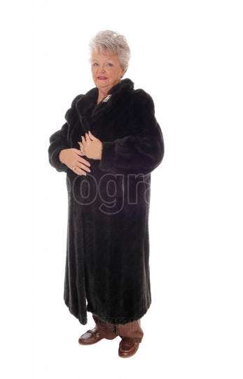 Senior woman standing in fur coat.
