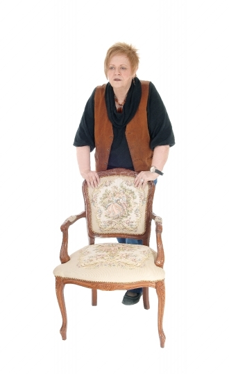 Senior woman standing on armchair.