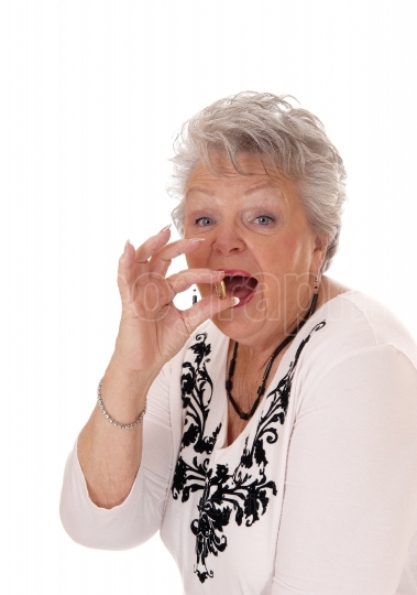 Senior woman swallowing vitamin pill.