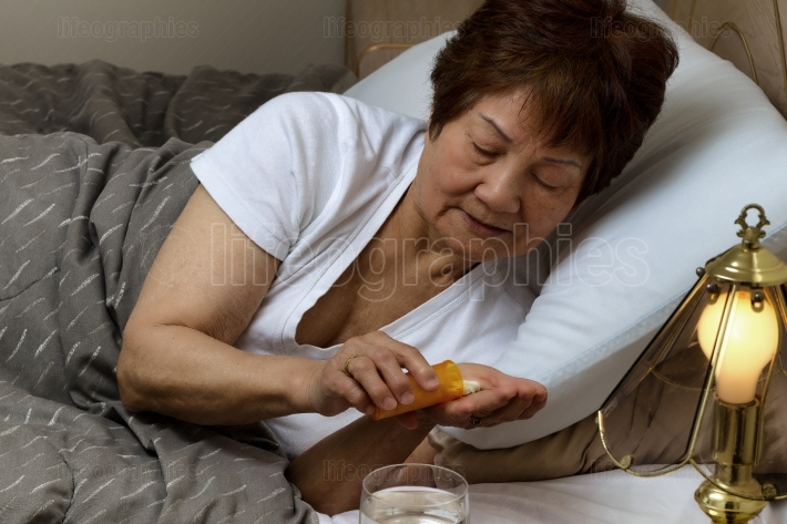 Senior woman taking her medicine at nighttime due to sickness