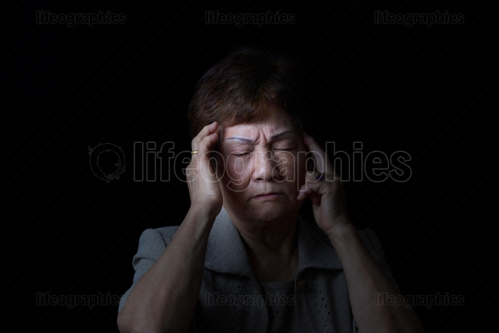 Senior woman touching her head while in pain on black background