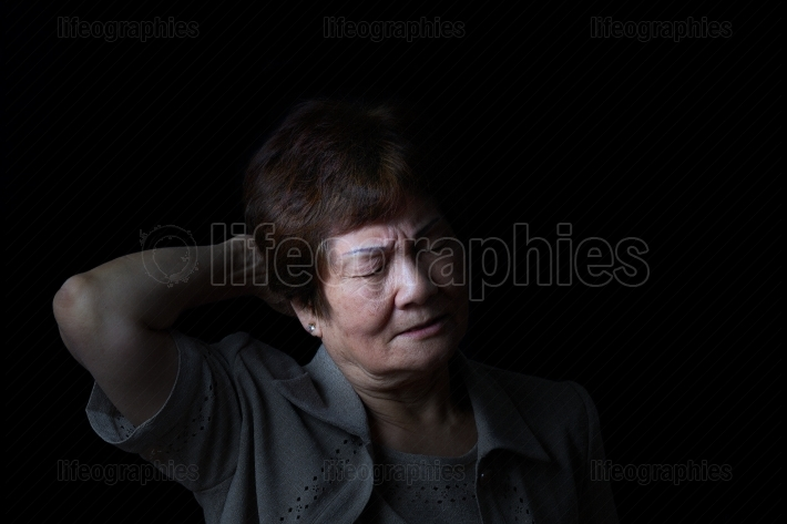 Senior woman touching the back of her head while in pain on blac