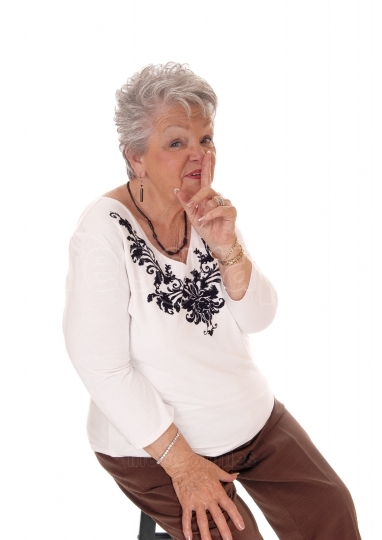 Senior woman with finger over mouth.