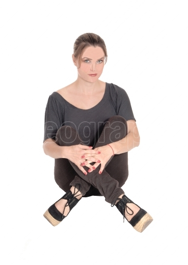 Serious looking woman sitting with closed legs on floor