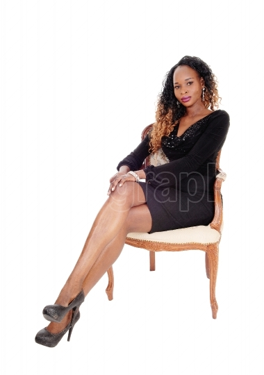 Serious woman sitting in armchair.