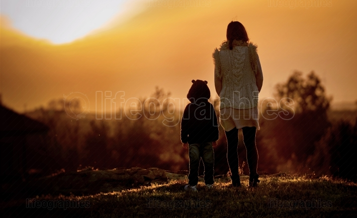 Silhouette of mother and daughter admiring sunset
