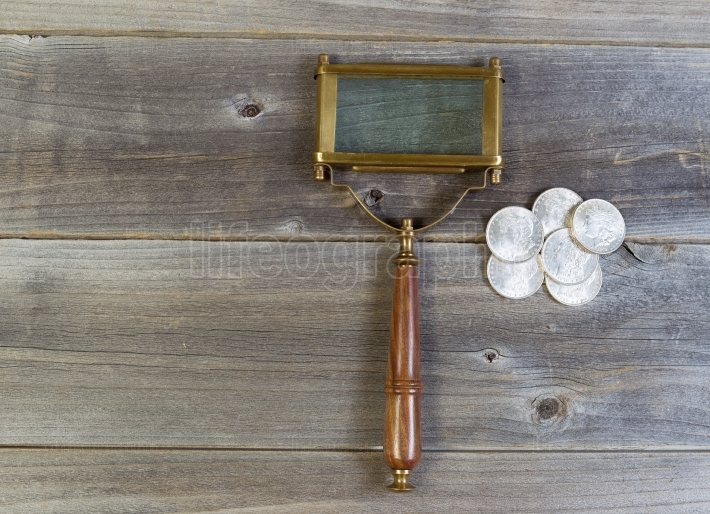 Silver Coins and Magnifying Glass on Wood