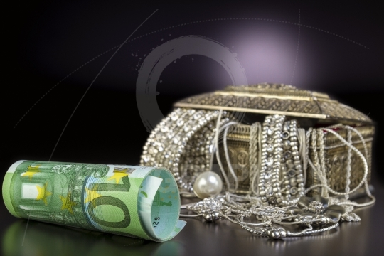 Silver jewelry and euro on black background