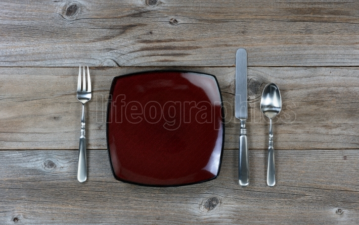 Simple dinner and silverware setting on rustic wood background