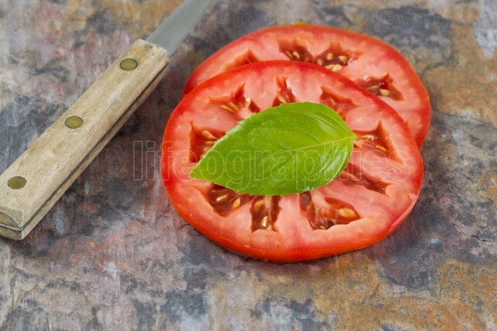 Single basil leaf and sliced tomato with knife on real stone boa