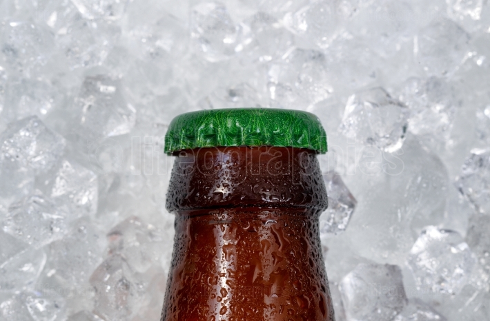 Single beer bottle cap cooling down on pile of ice