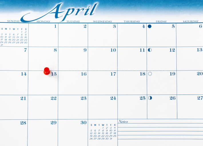 Single red pushpin on April 15 of calendar for tax income due da