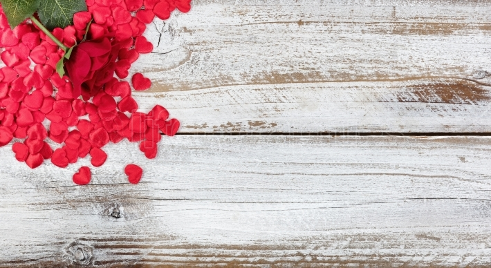 Single red rose and heart shapes resting on rustic white wood