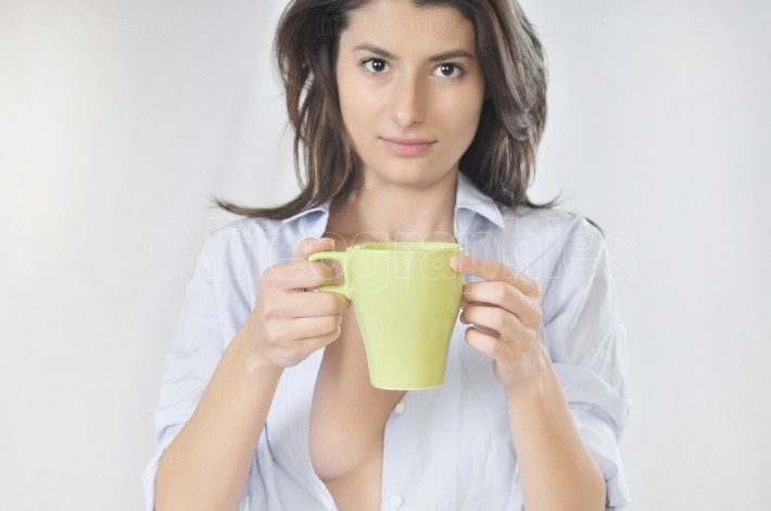 Sleepy woman with a cup of coffee in shirt