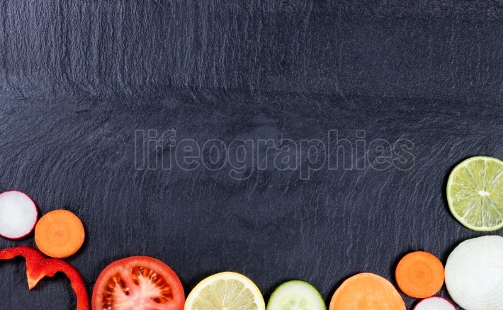 Slice vegetables and fruit on natural slate stone background
