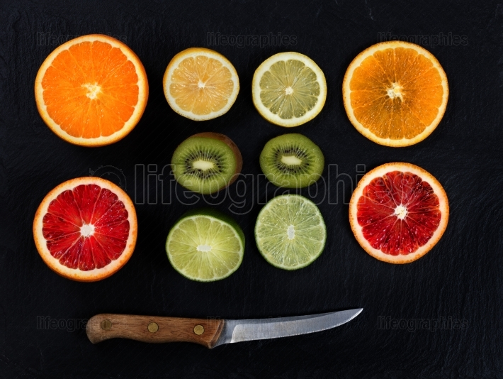 Sliced citrus fruit and knife on natural slate stone background
