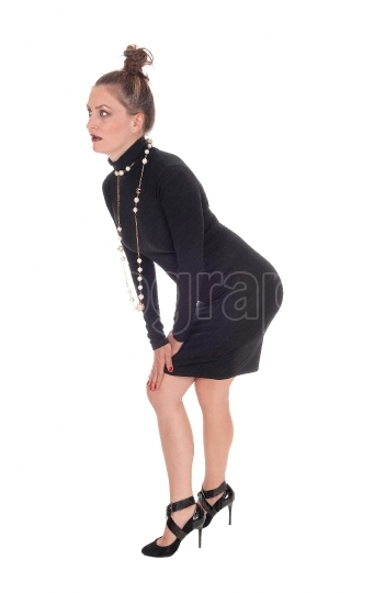 Slim woman in a black dress bending