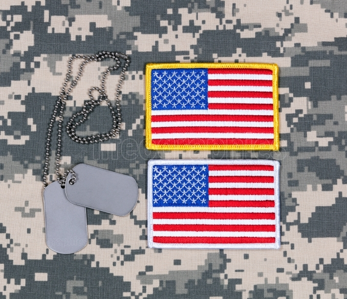 Small USA flag patches and ID tags on military battle dress unif
